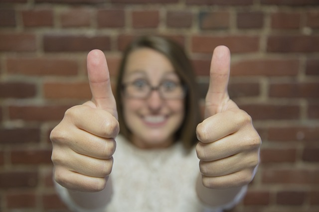 """Symbolbild: lachende Frau zeigt """"Daumen hoch!"""" mit beiden Händen"""