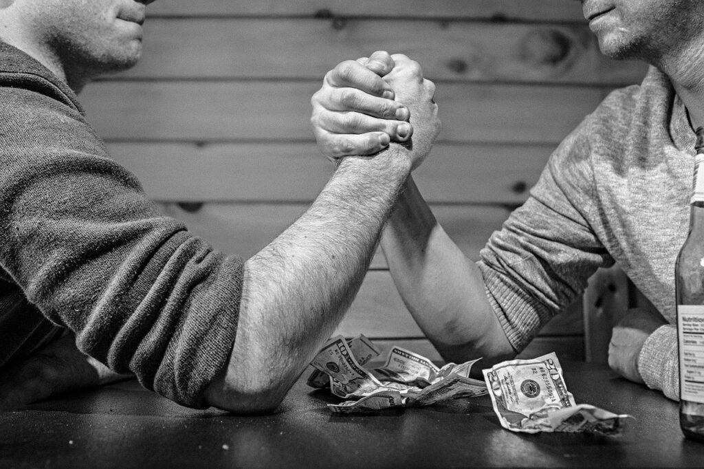 Sc hwarzweißbild: 2 Männer beim Armdrücken, zwischen ihnen Dollarscheine auf dem Tisch.