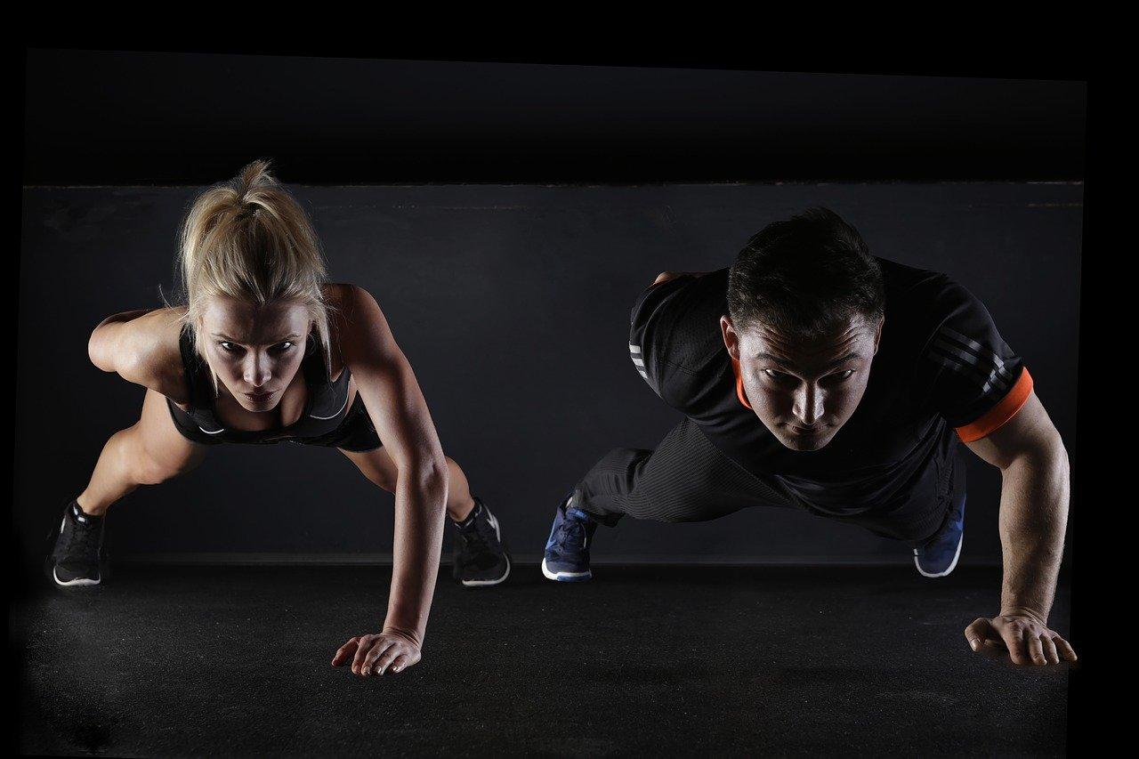 Symbolbild für Fitness nach COVID: eine Frau und ein Mann trainieren nebeneinander Push-ups